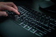 Man maskinskrivning på ett tangentbord med bokstäver i hebréiskt och engelskt Arkivbilder