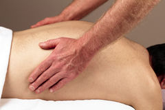 Man Massaging Back Sides. Male receiving a massage therapy from a male massage therapist Royalty Free Stock Photo