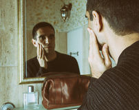 Man massaging cheek in front of mirror with brown leather toiletry bag Royalty Free Stock Photos
