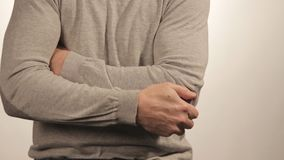 The man massaging the elbow due to acute pain on a white background stock video