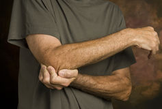 Man massaging elbow in pain_2 Stock Images
