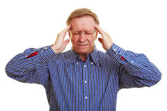 Man massaging his temples. Elderly man massaging his aching temples Stock Photography