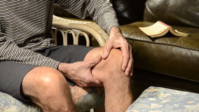 Man massaging knee in pain Royalty Free Stock Photo