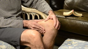 Man massaging knee in pain Stock Photo