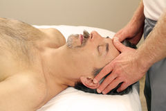 Man Massaging Male Face. Mature guy receiving a relaxing facial massage from a masseur at a day spa Stock Photos
