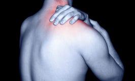Man massaging shoulder pain. Young man rubbing a sore shoulder muscle stock image