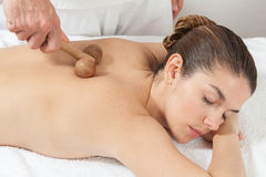 Man massaging a woman with a special tool Stock Image
