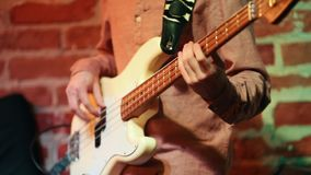 A man masterfully plays the guitar and dances at the evening in a jazz bar. Close up stock footage