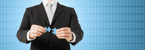 Man matching puzzle pieces over blue background Stock Photo
