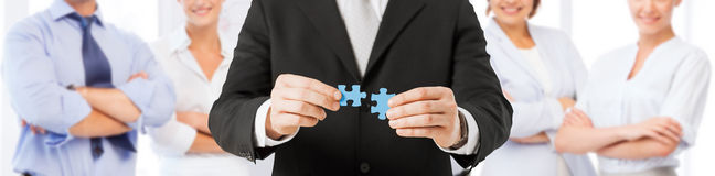 Man matching puzzle pieces over business team