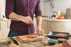 Man matlagning grillad biff på det hem- köket fotografering för bildbyråer