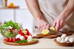 Man matlagning på kök som gör sund grönsaksallad, närbilden, selektiv fokus arkivbilder