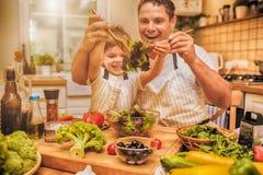 Man matlagning på köket med den lilla sonen arkivbild