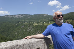 A man of mature age wearing sunglasses, bald, with a beard on th. E bridge against the background of the mountains Royalty Free Stock Image