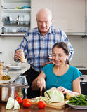 Man and mature  woman cooking lunch together Stock Image