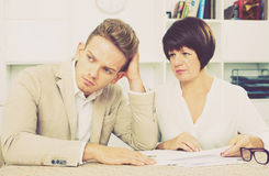 Man and mature woman sit at table. Depressed young men and mature women sit at table and discuss legal aspects of paperwork. Focus on the man Royalty Free Stock Photography