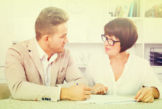 Man and mature woman sit at table Royalty Free Stock Photo