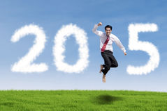 Man on meadow forming number 2015. Cheerful businessman jumping on meadow with cloud forming number 2015 Stock Images