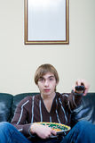 Man with meal. Near the TV set Royalty Free Stock Photography