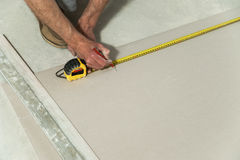 Man measures the drywall. To cut a piece required Royalty Free Stock Photo