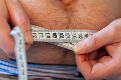 Man measures her abdomen with a measuring tape stock images