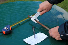 Man measures metal rod diameter with caliper. Nearby is roulette, pen and paper sheet Stock Photo
