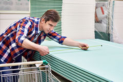 Man measures with roulette drywall sheets in store building mate Stock Photo