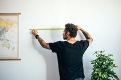Man measures wall with measuring tape stock photography