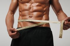 Man measuring abs with tape. Close-up muscular man measuring stomach and abs with tape in studio Royalty Free Stock Photography