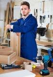 Man measuring boards for furniture at workshop Royalty Free Stock Image