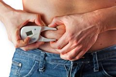 Man measuring body fat with caliper Royalty Free Stock Photo