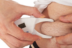 Man measuring body fat with caliper Royalty Free Stock Photography