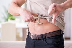 The man measuring body fat with calipers. Man measuring body fat with calipers Royalty Free Stock Photos