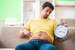 The man measuring body fat with calipers in time management concept. Man measuring body fat with calipers in time management concept royalty free stock image