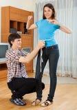 Man measuring girlriend waist Stock Image