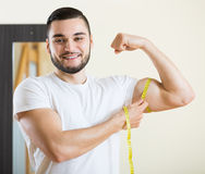 Man measuring his bicep and body Royalty Free Stock Images