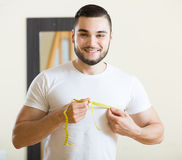 Man measuring his bicep and body Stock Image