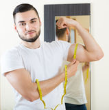 Man measuring his bicep and body Royalty Free Stock Image