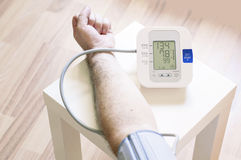 Man measuring his blood pressure. At home Royalty Free Stock Photography