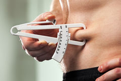 Man is measuring his body fat with calipers. Young man is measuring his body fat with calipers Royalty Free Stock Image