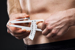 Man is measuring his body fat with calipers. Young man is measuring his body fat with calipers royalty free stock photos