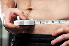 Man measuring his waist. Man measuring his waist with a measuring tape Royalty Free Stock Images