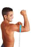 Man measuring muscle circumference. Young man measuring the circumference of his upper arm royalty free stock photography