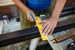 Man measuring off metal bar in workshop. Man measuring off metal bar in workshop Royalty Free Stock Image