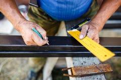 Man measuring off metal bar in workshop. Man measuring off metal bar in workshop Stock Photo