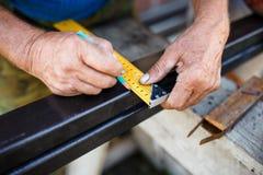 Man measuring off metal bar in workshop. Man measuring off metal bar in workshop Stock Image