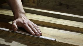 Man measuring wooden board with folding ruler in carpenters workshop. Man measuring recycled wooden board with folding ruler in carpenters workshop stock video