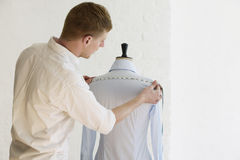 Man Measuring Shirt On Mannequin In Fashion Studio Royalty Free Stock Photos