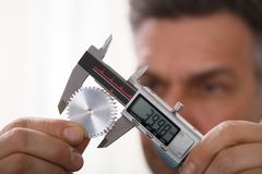 Man Measuring Size Of Gear With Digital Vernier Caliper. Close-up Of A Man`s Hand Measuring Gear`s Size With Digital Electronic Vernier Caliper royalty free stock photo