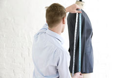 Man Measuring Suit On Dressmaker's Model In Studio Stock Images
